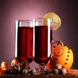 Stock Photo: Mulled wine in glasses, spice and orange on wooden table on purple back