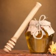 Jar of honey and wooden drizzler on table on yellow background — Stock Photo