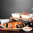 Delicious sushi on plate, chopsticks, soy sauce, fish and shrimps on bamboo — Stock Photo #8817127