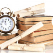 Foto Stock: Pile of old books with clock and scroll isolated on white