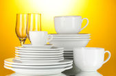 Empty bowls, plates, cups and glasses on yellow background — Stock Photo