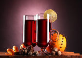 Mulled wine in the glasses, spice and orange on wooden table on purple back — Stock Photo