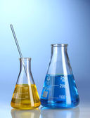 Two flasks with yellow and blue liquid with reflection on blue background — Stock Photo