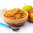 Tasty cornflakes in wooden bowl, apples and glass of milk isolated on white — Stock Photo