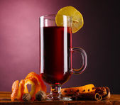 Mulled wine in the glass, spice and lemon on purple background — Stock Photo