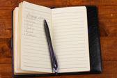 Shoping lijst en pen op houten tafel — Stockfoto