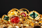 Various gold jewellery on black background — Stock Photo