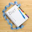 Planning of diet. Notebook measuring tape and pen on wooden table — Stock Photo #8856334