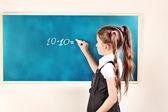 Beautiful little girl writing on classroom board — Stock Photo