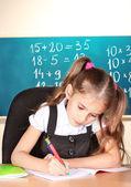 Little schoolchild in classroom near blackboard — Stock Photo