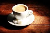 Filiżanka kawy i cukru na drewnianym stole — Zdjęcie stockowe
