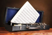 Old clarinet and notebook with notes in case on wooden table on brown backg — Stock Photo