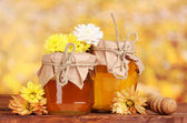 Two jars of honey and wooden drizzler on table on yellow background — Stock Photo