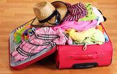 Ouvrir la valise rouge avec des vêtements dans la chambre — Photo