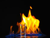 Flaming vodca on black background — Stock Photo
