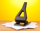 Nero ufficio perforatore con carta su sfondo giallo — Foto Stock