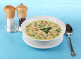 Tasty soup on blue tablecloth isolated on white — Stock Photo