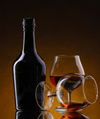 Glasses of brandy and bottle on brown background — Stock Photo