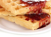 Tasty waffles with jam on plate close-up isolated on white — Stock Photo