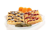 Sweet waffles with jam and chocolate on plate isolated on white — Stock Photo