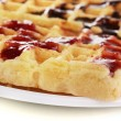 Sweet waffles with jam and chocolate on plate close-up isolated on white - Stock Photo