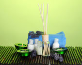 Air freshener, bottles, towel and candles on bamboo mat on green background — Stock Photo