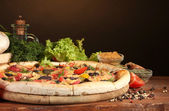 Delicious pizza, vegetables and spices on wooden table on brown background — Stock Photo