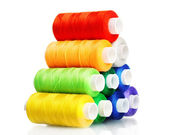 Pyramid of many-coloured bobbins of thread isolated on white — Stock Photo