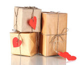 Three parcels with blank heart-shaped labels isolated on white — Stock Photo