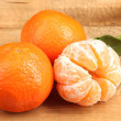 Tangerines with leaf on wooden table — Stock Photo
