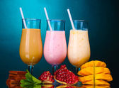 Milk shakes with fruits and chocolate on blue background — Stock Photo