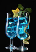 Blue cocktail in glasses on black background — Stock Photo