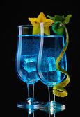 Cóctel en vasos sobre fondo negro azul — Foto de Stock