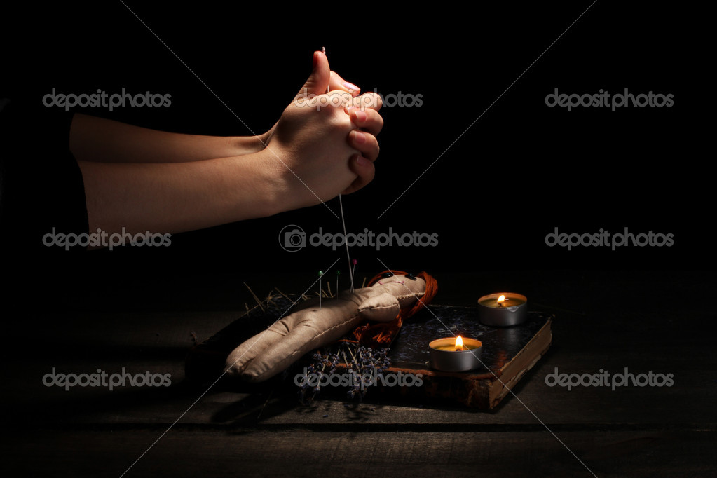 Voodoo doll girl pierced by a needle on a wooden table in the candlelight — Stock Photo #8895435