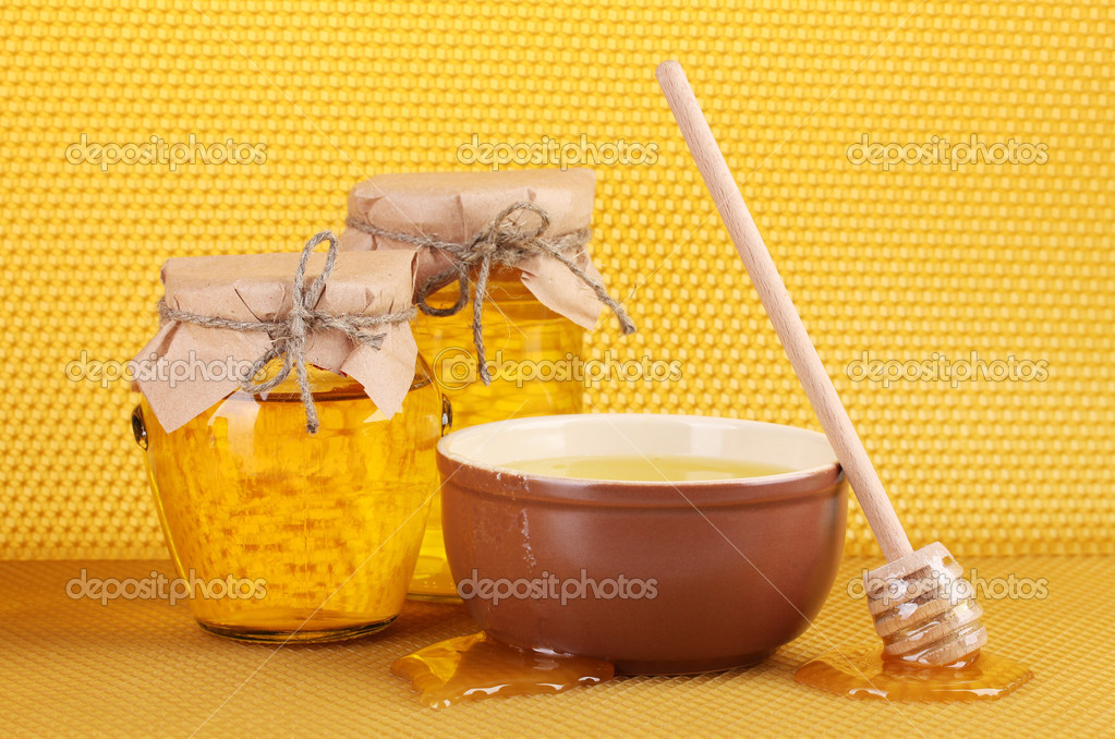 Jars of honey, bowl and wooden drizzler with honey on yellow honeycomb background — Stock Photo #8896838
