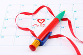 Calendar page with hearts, pen and ribbon on St.Valentines Day — Stockfoto