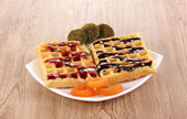 Sweet waffles with jam and chocolate on plate on wooden background — Stock Photo