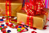 Colorful gift bags and gifts with confetti close-up isolated on white — Stock Photo