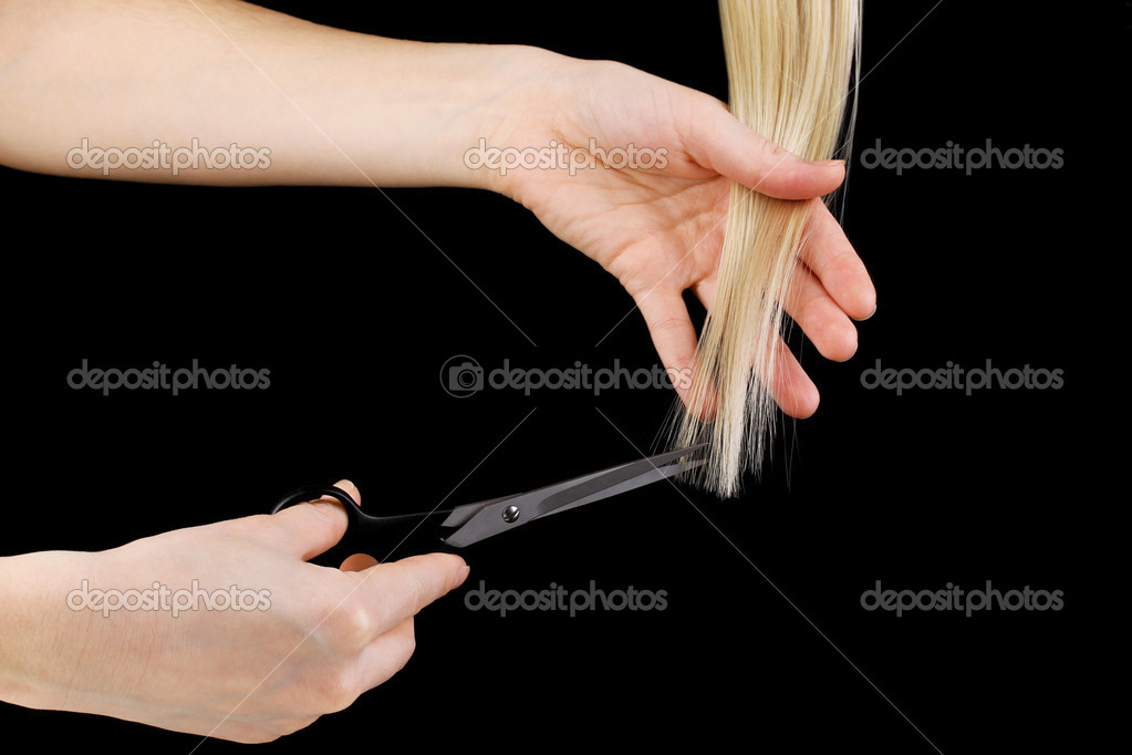 Shiny blond hair in hairdresser's hands isolated on black — Stock Photo #8905602