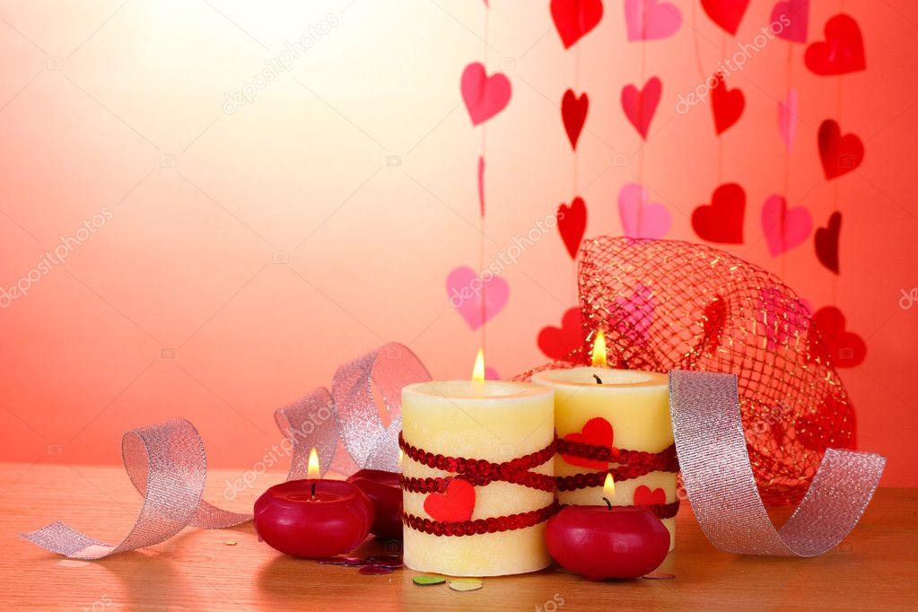Candles for Valentine's Day on wooden table on red background — Stock Photo #8911495