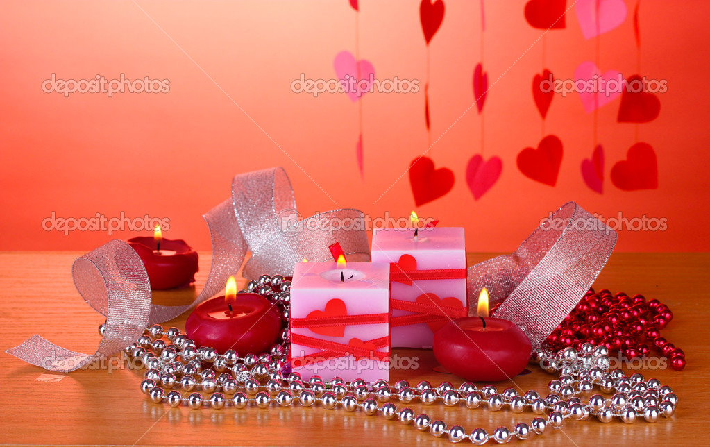Candles for Valentine's Day on wooden table on red background — Stock Photo #8911512