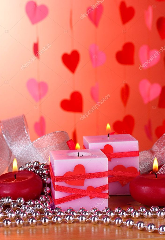 Candles for Valentine's Day on wooden table on red background  Stock Photo #8911533
