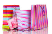 Colorful gift bags and gifts with confetti isolated on white — Stock Photo