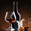Glasses of brandy and bottle on brown background — Stock Photo #8931307