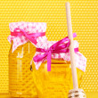 Jars of honey and wooden drizzler on yellow honeycomb background — Stock Photo #8931333