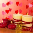 Beautiful candles with romantic decor on a wooden table on a red background - Stockfoto
