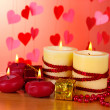 Beautiful candles with romantic decor on a wooden table on a red background - Foto Stock