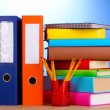 Bright office folders and books with stationery on wooden table on blue bac — Stock Photo