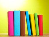 Böcker på träbord på grön bakgrund — Stockfoto