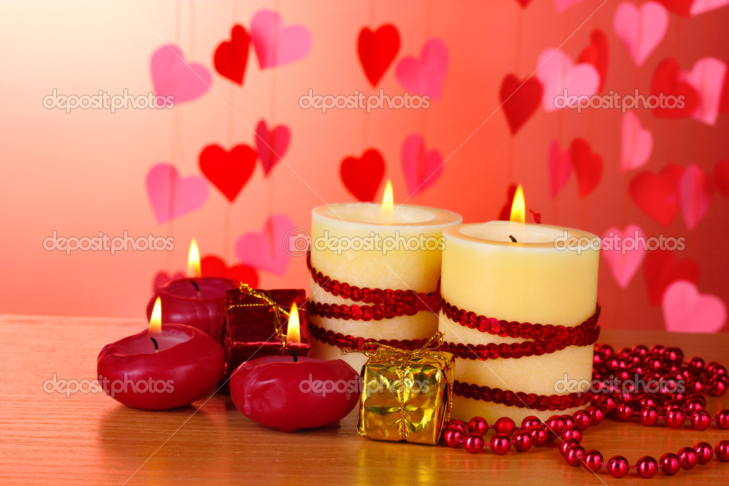 Beautiful candles with romantic decor on a wooden table on a red background  Stock Photo #8931362